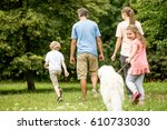 family and girl walking dog in... | Shutterstock . vector #610733030