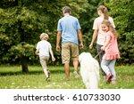 family and girl walking dog in... | Shutterstock . vector #610733030