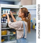 Small photo of Accurate and beautiful girl standing near fridge in kitchen