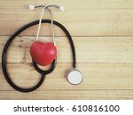 Small photo of red heart and stethoscope on wood table, world health day concept, process vintage tone