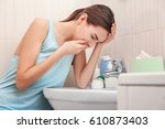 young vomiting woman near sink... | Shutterstock . vector #610873403