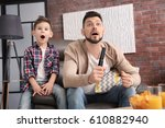 father and son watching sports... | Shutterstock . vector #610882940