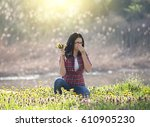 Small photo of Young woman holding wildflowers bouquet in dandelion field and sneezing in tissue. Seasonal allergens affecting people