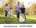 family playing soccer in park... | Shutterstock . vector #610914800
