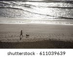 Stock photo silhouette of a dog walker with dog on holywell beach cornwall uk 611039639