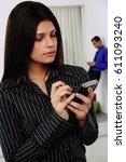 Small photo of Businesswoman using PDA, people in the background