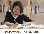woman studying in library | Shutterstock . vector #611093888