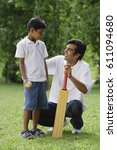 a father and son play cricket... | Shutterstock . vector #611094680