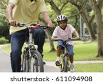a father and son ride their... | Shutterstock . vector #611094908