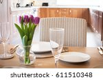 table setting with tulips in... | Shutterstock . vector #611510348