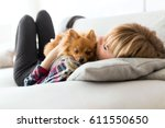 Stock photo portrait of beautiful young woman with dog playing at home 611550650