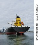 Small photo of Large products Tanker discharging at the Oil Terminal of Lorient, France,with black hull and yellow funnel on cloudy day. Stern view.