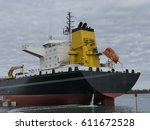 Small photo of Large products Tanker discharging at the Oil Terminal of Lorient, France,with black hull and yellow funnel on cloudy day. Stern view of the aft part.