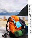 Tourists backpack on a pier in Norwagian fjords - stock photo