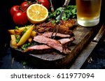 steak with herbs and beer on a... | Shutterstock . vector #611977094