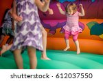 Small photo of Cute little girl jumping inside the inflatable bouncy castle