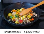 Small photo of Stirring bell peppers, tofu, farro and garbanzo beans mix in cast iron skillet with a wooden spoon- healthy cooking concept