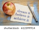 Small photo of dream, believe, achieve it concept - handwriting on a napkin with a fresh apple