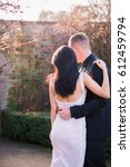Small photo of Stylish, hugging couple stands aback on the yard