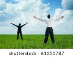 happy businesspeople standing on green grass and looking up - stock photo