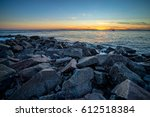 waves and a jetty at sunset in... | Shutterstock . vector #612518384