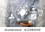 Small photo of Online education concept. Man offers smart phone with bulb gear icon on virtual screen. Business e-learning. Learning workshop and presentation learn to think internet training knowledge technology.