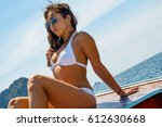 young woman in a bikini sits on ... | Shutterstock . vector #612630668