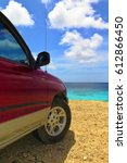 Off road red vehicle on the yellow tropical beach. Car looking on the sea, azure calm sea surface. Bright colors, white clouds, sunny day, serene beach holiday scene.