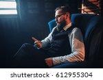 man sitting in armchair ... | Shutterstock . vector #612955304
