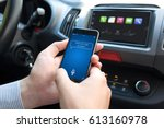 man hand in car holding phone... | Shutterstock . vector #613160978