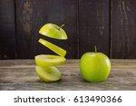 two green apples .sliced apple... | Shutterstock . vector #613490366
