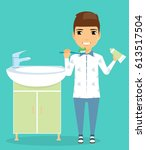a boy stands near the sink. in... | Shutterstock .eps vector #613517504