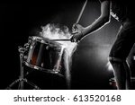 Small photo of man plays musical percussion instrument with sticks closeup on a black background, a musical concept with the working drum, beautiful lighting on the stage