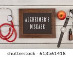 "Small photo of Medecine concept - blackboard with text ""Alzheimer's disease"", watch and stethoscope on white wooden background"