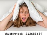 Small photo of Young woman with insomnia covering head and ears with pillow