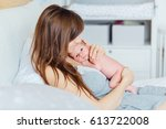 mother holding newborn baby and ... | Shutterstock . vector #613722008