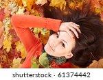 Girl in autumn orange leaves.  Outdoor. - stock photo