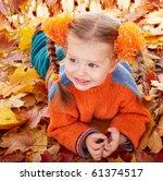 Girl child in autumn orange leaves. Outdoor. - stock photo