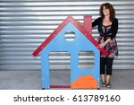 woman next to a small house for ... | Shutterstock . vector #613789160