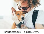 Young trendy hipster with tattoos crazy curly hair with his best friend a cute small basenji puppy gives him a tender kiss on ears while hugs him with his arms - stock photo