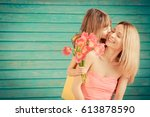 woman and child with bouquet of ... | Shutterstock . vector #613878590