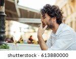 handsome elegant man sitting... | Shutterstock . vector #613880000