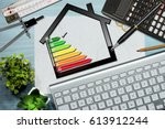 Small photo of Energy efficiency rating graph on a desk with a house model, calculator, folding ruler, drawing compass, pencils and a computer keyboard