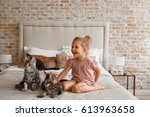 Stock photo little cute girl playing with kitten on sofa at home 613963658