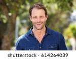 Small photo of Close up portrait of cool guy smiling outside