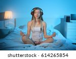 Stock photo young woman meditating and listening to music while sitting on bed at home 614265854