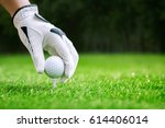 hand putting golf ball on tee... | Shutterstock . vector #614406014