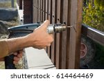 man hands drilling wooden fence ... | Shutterstock . vector #614464469