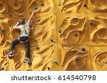 child climbing a rock wall... | Shutterstock . vector #614540798