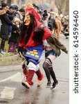 Small photo of STUTTGART, GERMANY - FEBRUARY 28: a dreadful witch mask in parade makes a fake abduction a girl. Shot under light rain at Carnival parade in city center on feb 28, 2017 Stuttgart, Germany